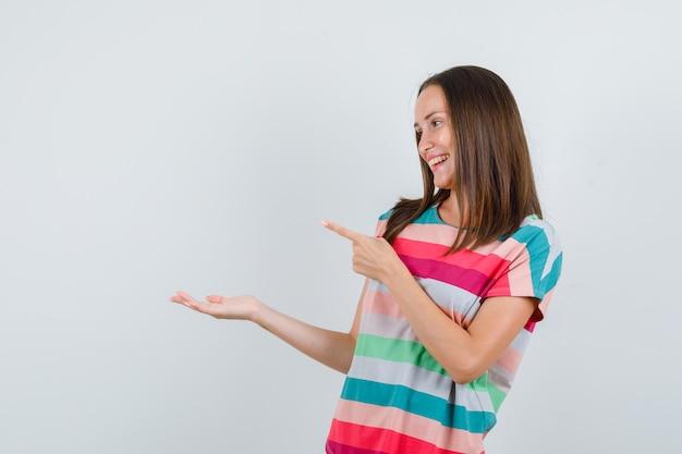 Giovane donna che punta lontano con il palmo della mano da parte in t-shirt e guardando allegro, vista frontale.