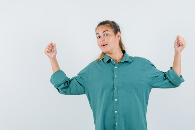Giovane donna che indica indietro in camicia blu e che sembra interessata