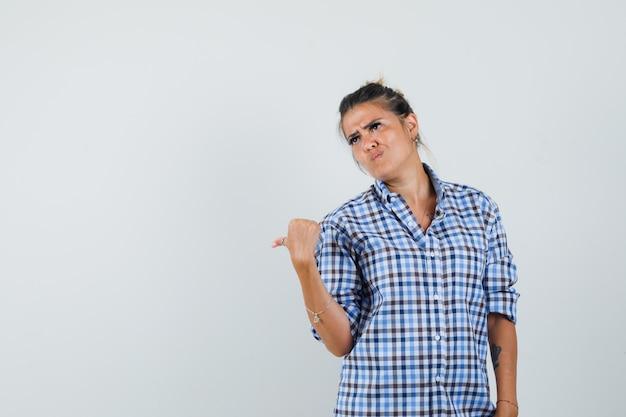 Giovane donna che punta indietro in camicia a scacchi e sembra riluttante