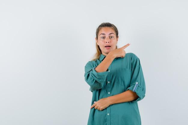 Молодая женщина, указывая назад в синей рубашке