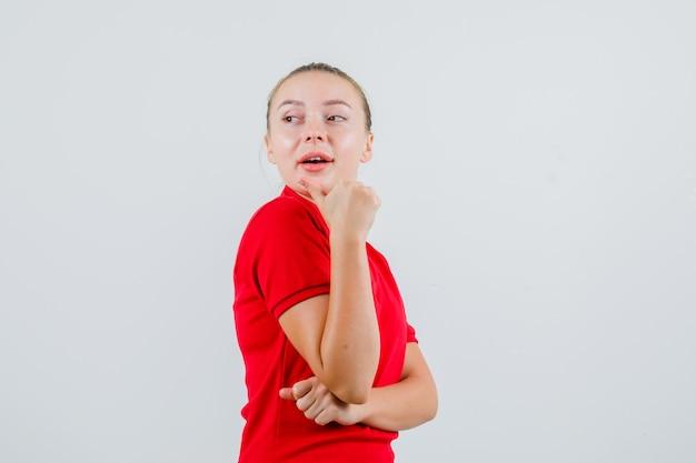 赤いtシャツを着て親指で後ろを向いて好奇心旺盛な若い女性