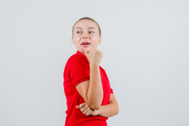 Young woman pointing back with thumb in red t-shirt and looking curious