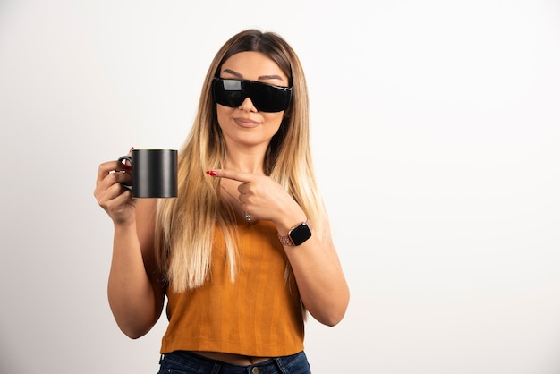 Young woman pointing at black cup and wearing goggles.
