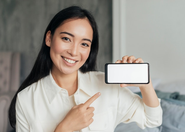 Young woman pointing to a blank phone