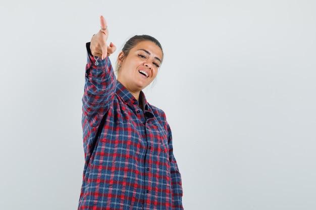 Giovane donna che punta alla telecamera con il dito indice in camicia a quadri e sembra carina, vista frontale.