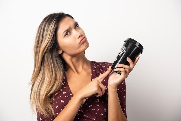 Giovane donna che punta a una tazza di bevanda sul muro bianco.