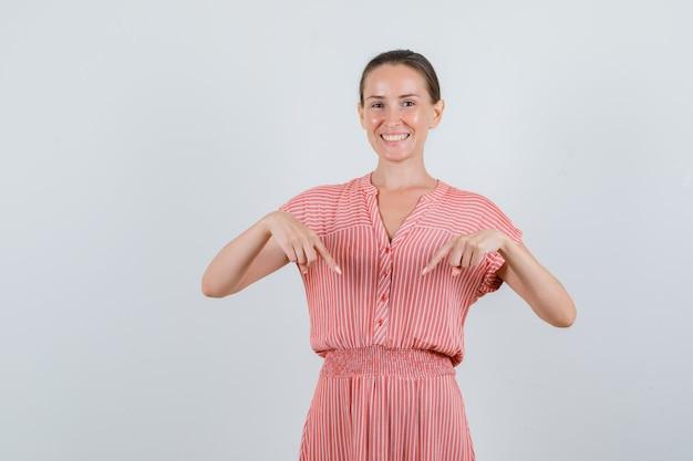 縞模様のドレスを下に向けて陽気に見える若い女性、正面図。
