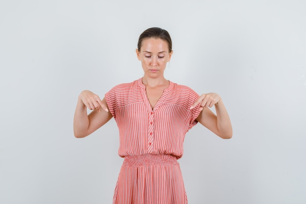 Молодая женщина, указывая вниз в полосатом платье и глядя сосредоточенно, вид спереди.