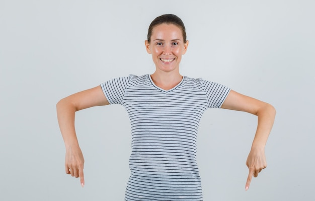 若い女性がtシャツを下に向けて幸せそうに見える、正面図。