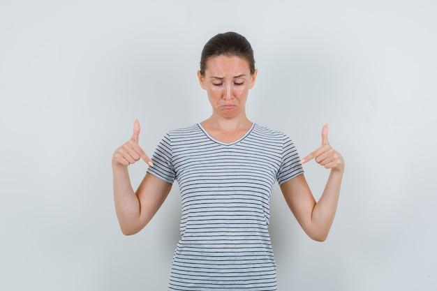 若い女性がtシャツを下に向けて動揺している、正面図。