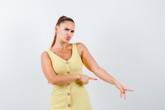 Giovane donna rivolta verso il basso, labbra imbronciate in abito giallo e guardando cupo