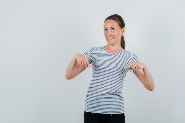Young woman pointing down and showing tongue in t-shirt, pants and looking hopeful. front view.