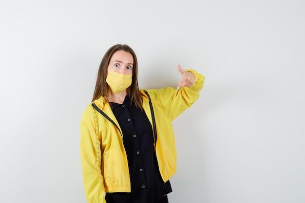 Молодая женщина, указывая вниз указательным пальцем и серьезно выглядящая