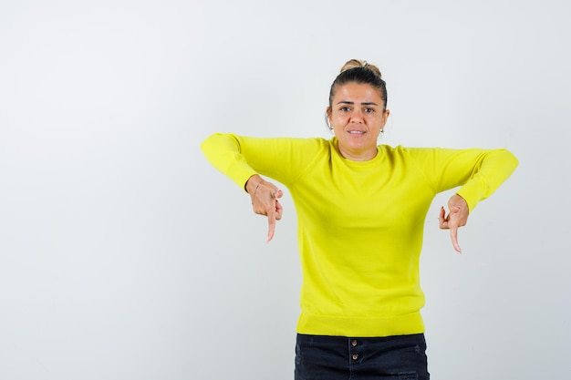 Молодая женщина указывает вниз указательными пальцами в желтом свитере и черных брюках и выглядит обеспокоенной