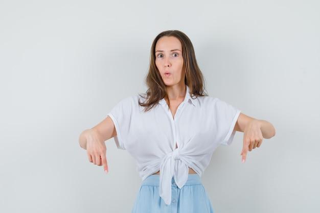 Giovane donna rivolta verso il basso con il dito indice in camicetta bianca e gonna azzurra e guardando sorpreso