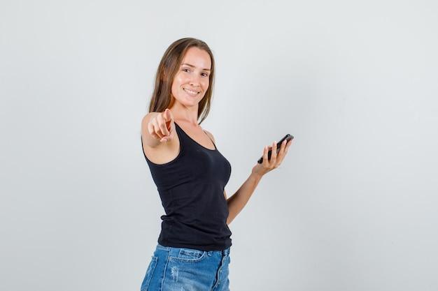 一重項、ショートパンツ、陽気に見えるスマートフォンでカメラに指を指している若い女性。 。