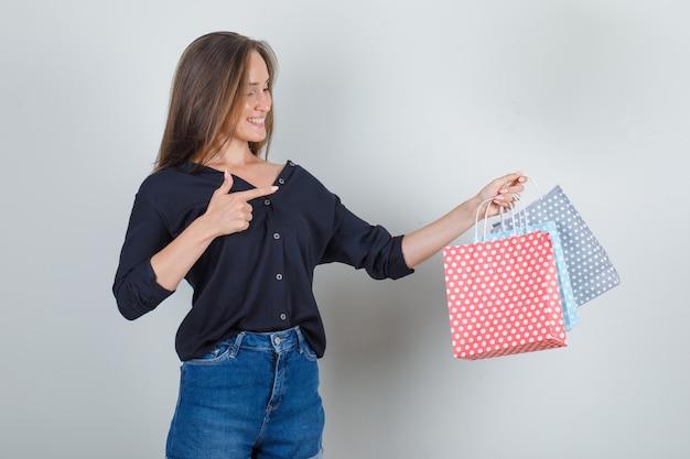 黒のシャツ、ジーンズのショートパンツで紙袋に指を指して、うれしそうに見える若い女性