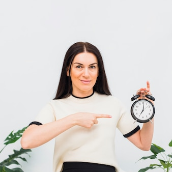 Young woman pointing finger at clock