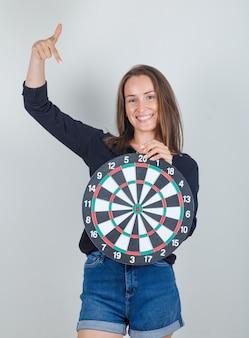 Giovane donna che punta il dito al bersaglio in camicia nera, pantaloncini di jeans e sembra allegro