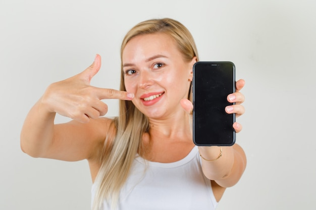 Giovane donna puntare il dito sullo smartphone in singoletto e guardando allegro.