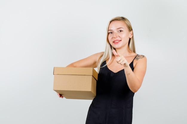 黒の一重項のボックスと幸せそうに見えるカメラに指を指している若い女性