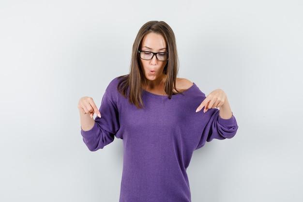 보라색 셔츠에 아래로 손가락을 가리키고 호기심을 찾고 젊은 여자. 전면보기.
