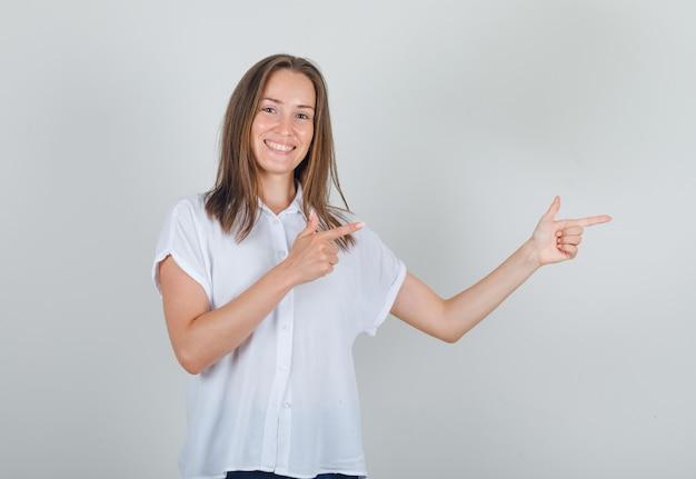 白いtシャツで指を横に向けて陽気に見える若い女性