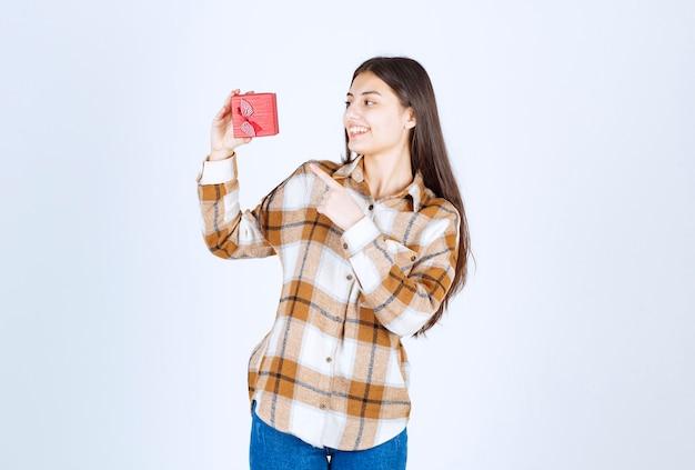 Giovane donna che punta al regalo sul muro bianco.