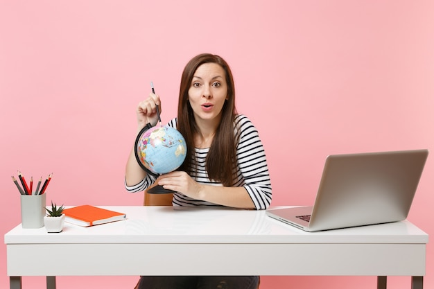 Young woman pointing on globe with pencil, planning vacation while sit and work at white desk with contemporary pc laptop