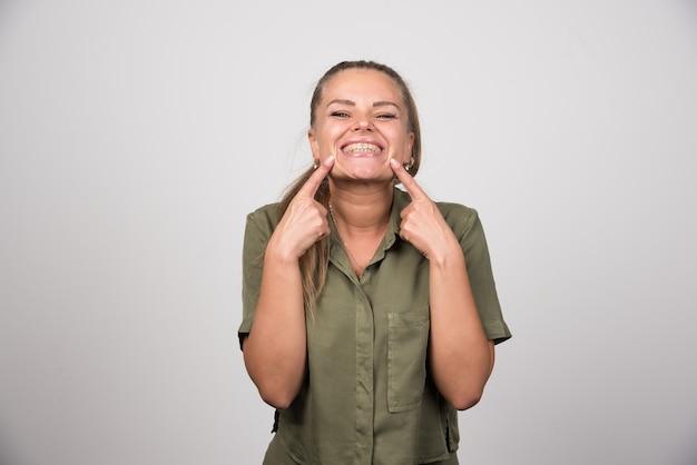 Giovane donna che indica la sua guancia sul muro grigio.