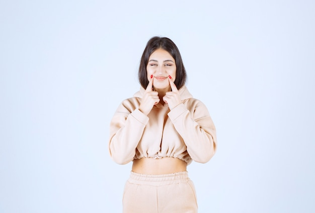 Young woman pointing her mouth and meaning her smile or oral hygiene