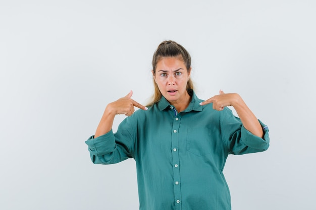 Young woman pointing at herself in blue shirt and looking aggressive