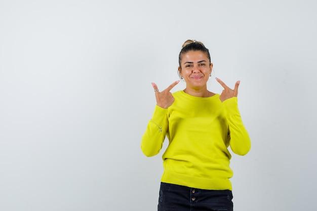 黄色いセーターと黒いズボンで自分を指して幸せそうに見える若い女性