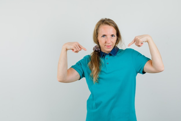 Giovane donna che punta a se stessa in maglietta e guardando orgoglioso