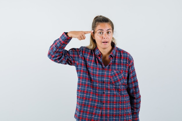 Giovane donna che punta a se stessa con il dito indice in camicia a quadri e che sembra seria
