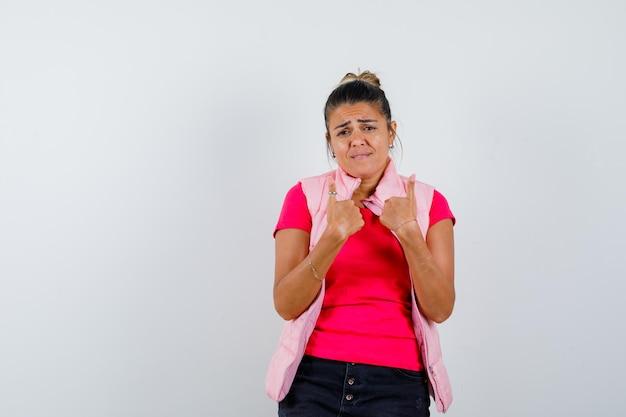 Giovane donna che indica se stessa con l'indice in maglietta e giacca rosa e sembra imbronciata