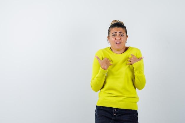 Giovane donna che si indica con un maglione giallo e pantaloni neri e sembra tormentata