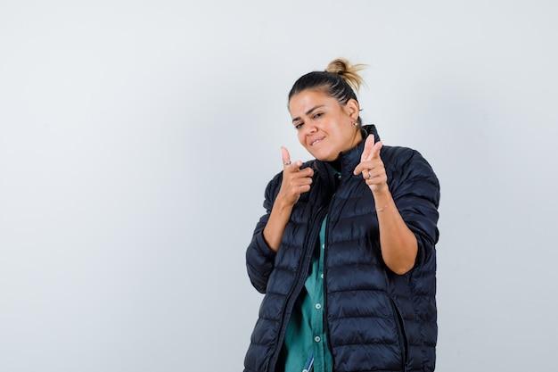 シャツ、ダウンジャケットを指して、陽気に見える若い女性。正面図。