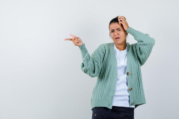 Giovane donna che punta a sinistra con il dito indice mentre tiene la mano sulla testa in camicia bianca e cardigan verde menta e sembra tormentata
