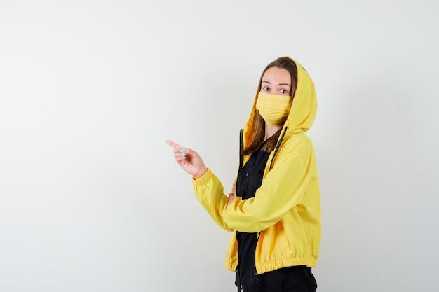 Giovane donna che punta a sinistra con il dito indice