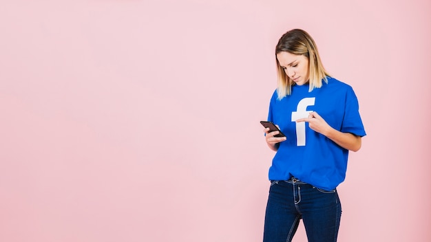 Young woman pointing at mobile phone over pink background