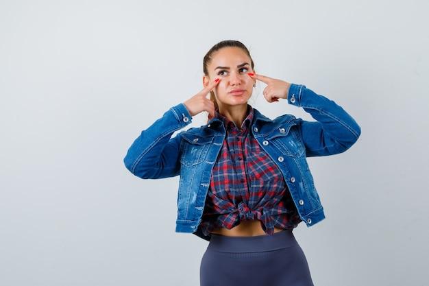 市松模様のシャツ、ジーンズのジャケットで指で目を指して、物欲しそうな正面図を探している若い女性。