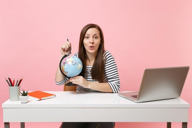 パステルピンクの背景に分離された現代的なpcラップトップで白い机に座って仕事をしながら休暇を計画し、鉛筆で地球を指している若い女性。業績ビジネスキャリア。スペースをコピーします。