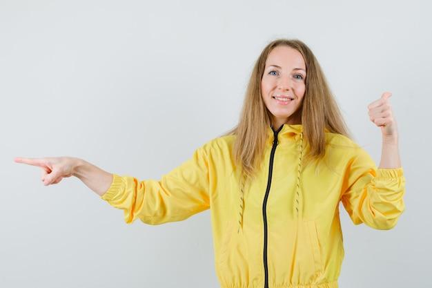 黄色のボンバージャケットとブルージーンズで反対方向を指し、楽観的な正面図を探している若い女性。