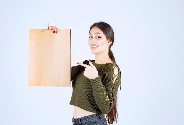 Giovane donna che punta a un sacco di carta su sfondo bianco.
