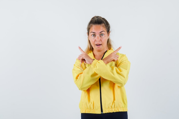 Young woman pointing at reverse sides in yellow raincoat and looking serious
