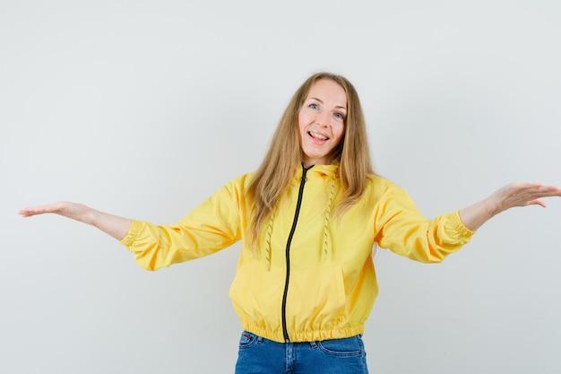 黄色のボンバージャケットとブルージーンズで腰に片手を持ち、楽観的に見える若い女性。正面図。