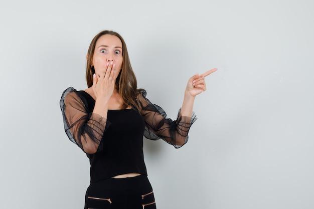Giovane donna che punta a destra con il dito indice e che copre la bocca con la mano in camicetta nera e pantaloni neri e sembra sorpresa. vista frontale.