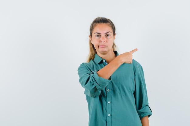 人差し指で右を指して、緑のブラウスで唇を曲げて、真剣に見える若い女性 無料写真