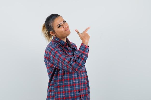 チェックシャツを着た人差し指で右を指してきれいに見える若い女性。正面図。